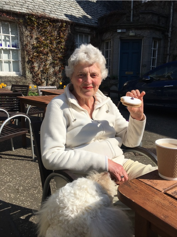 Older lady sitting outdoors having cake and coffee in the sun